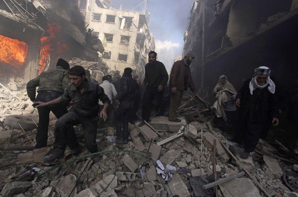 Foto: Habitantes de la zona de Douma, en el extrarradio de Damasco, caminan por los escombros de un bombardeo del régimen sirio, en febrero de 2015 (Reuters)
