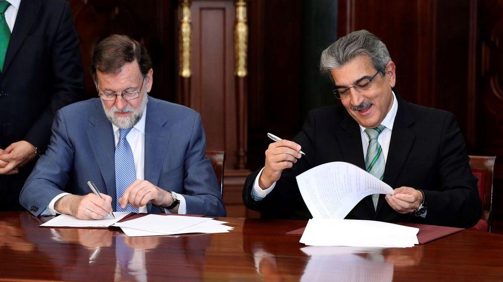 Foto: El presidente del Gobierno, Mariano Rajoy, y el de Nueva Canarias, Román Rodríguez, firman el acuerdo para los PGE. (EFE)