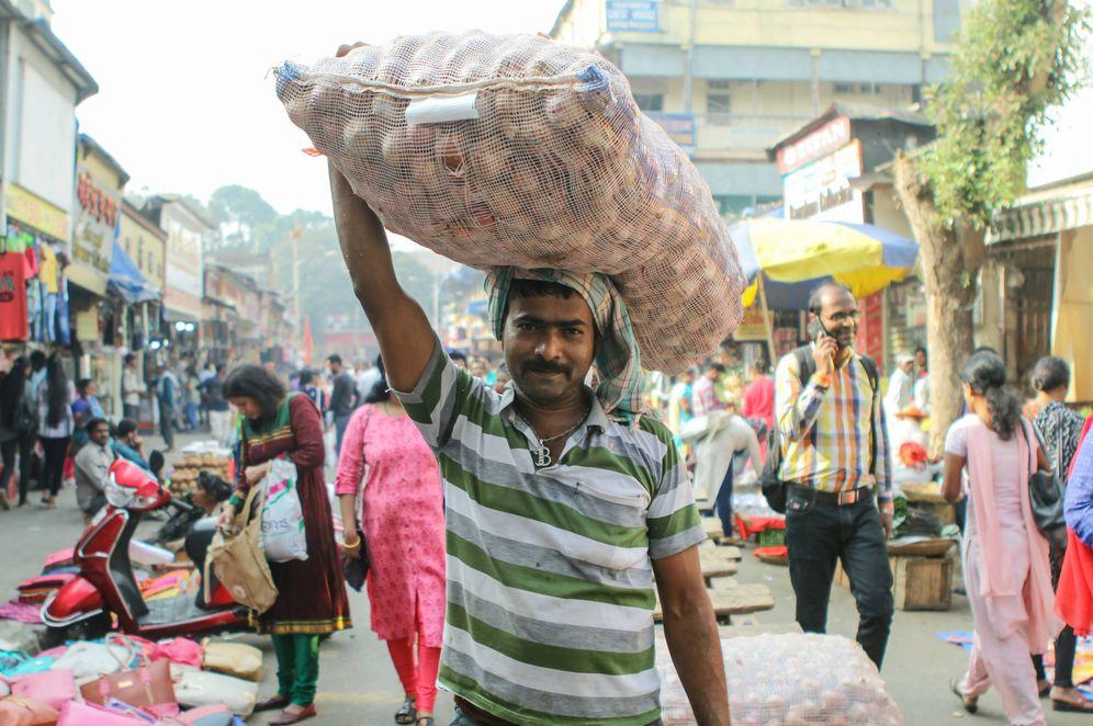 Foto: Un campesino indio con un saco de cebollas en la cabeza.
