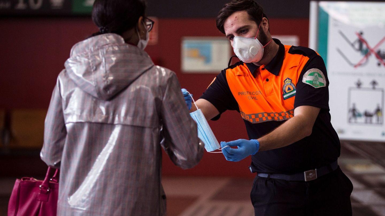Este miembro de Protección Civil entrega correctamente una mascarila. (Foto: EFE)