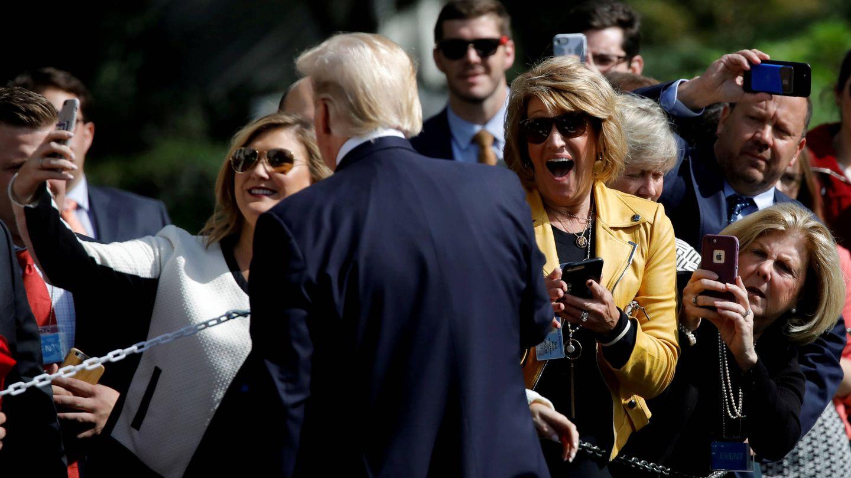 Donald Trump posa antes unos visitantes a la Casa Blanca antes de partir de viaje hacia Dallas. (Reuters)
