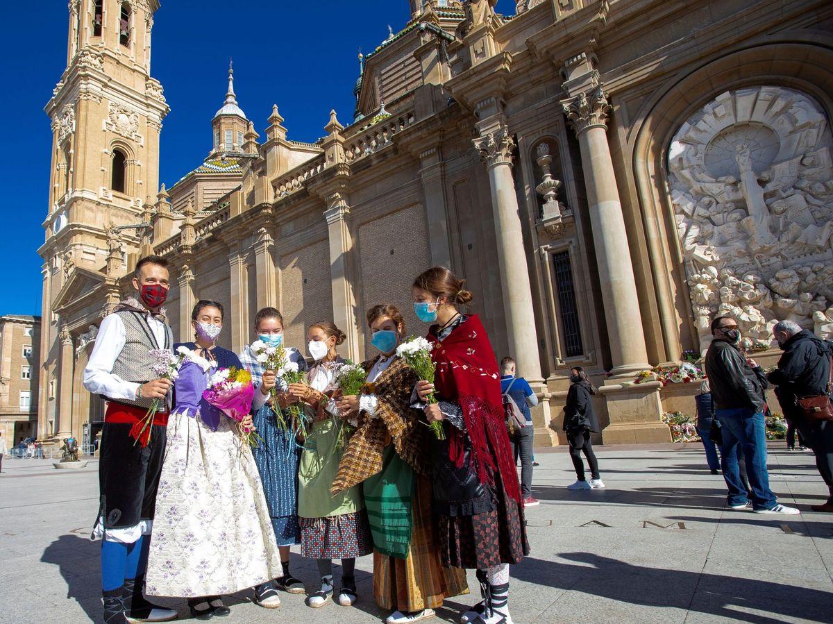 Foto: Varias personas depositan ramos de flores en la basílica del Pilar en Zaragoza (EFE)