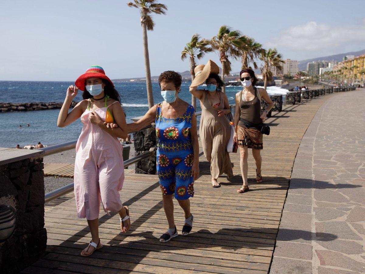 Foto: Turistas caminan por un paseo cercano a la playa de Las Caletillas, en el municipio de Candelaria (Tenerife).  (EFE)