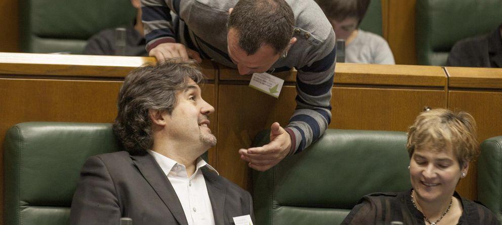 Foto: Los parlamentarios de EH Bildu Peio Urizar (i) y Unai Urruzuno conversan durante un pleno del Parlamento vasco. (Efe)