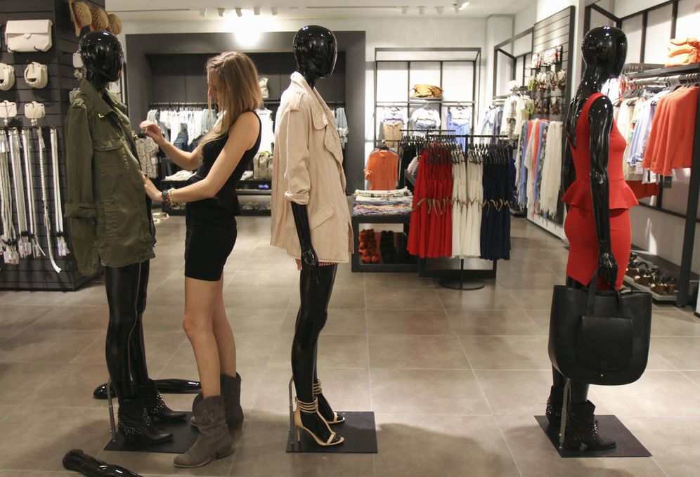 Foto: Una dependienta viste un maniquí en una tienda de Zara en Arteixo, La Coruña. (Reuters)
