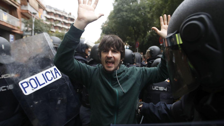 Foto: Agentes antidisturbios de la Policía Nacional forman un cordón de seguridad frente al colegio Ramón Llull de Barcelona. (EFE)