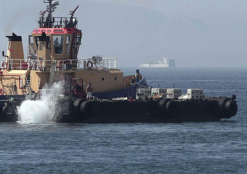 Foto: Un remolcador de Gibraltar lanzando al mar bloques de hormigón. (efe)