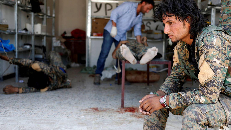 Un miliciano de las Fuerzas Democráticas Sirias ante varios camaradas heridos en combates contra ISIS, en Raqqa. (Reuters)