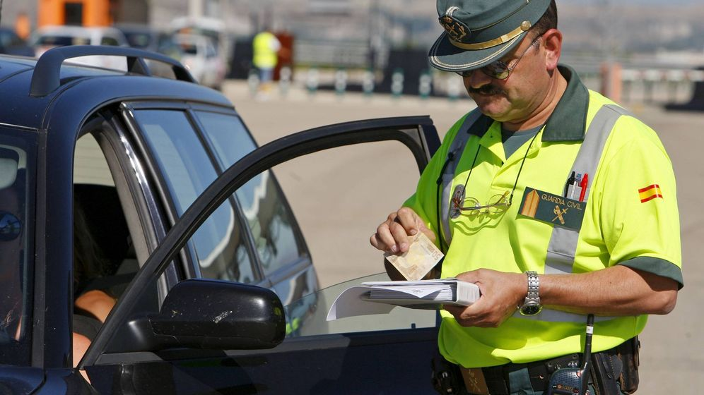 Foto: Un guardia civil, poniendo una multa por velocidad. (EFE)