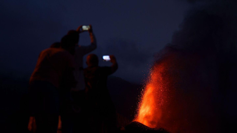 Cuatro personas contemplan desde una montaña al caer la noche la lava que sale proyectada hacia el cielo del nuevo volcán de La Palma. (EFE)