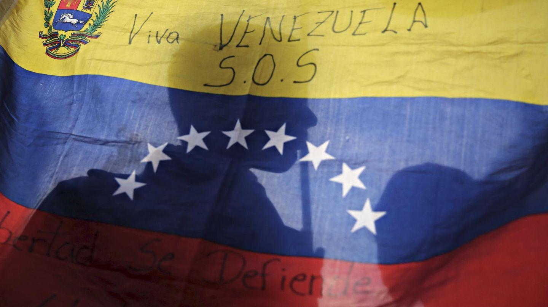 La silueta de un opositor a través de una bandera venezolana durante un mitin electoral en Caracas (Reuters).