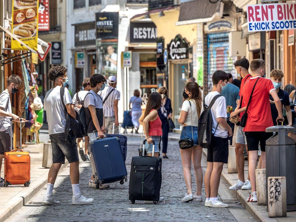 Foto: Gente esperando con sus maletas en Valencia. (EFE)