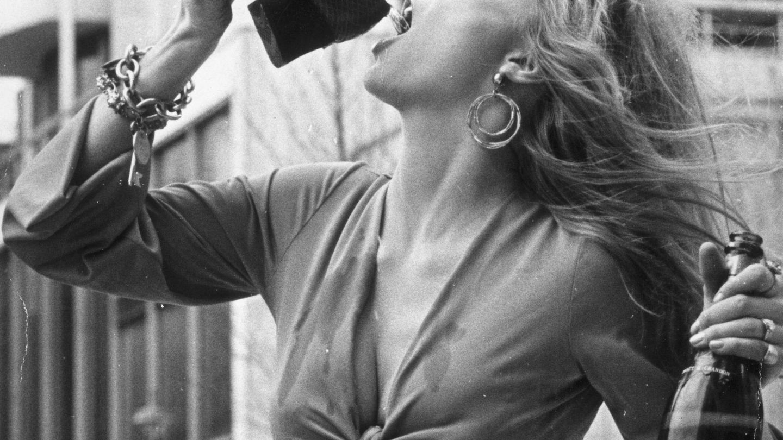 La modelo Vicki Hodge, bebiendo champán con su melena al viento. (Getty)