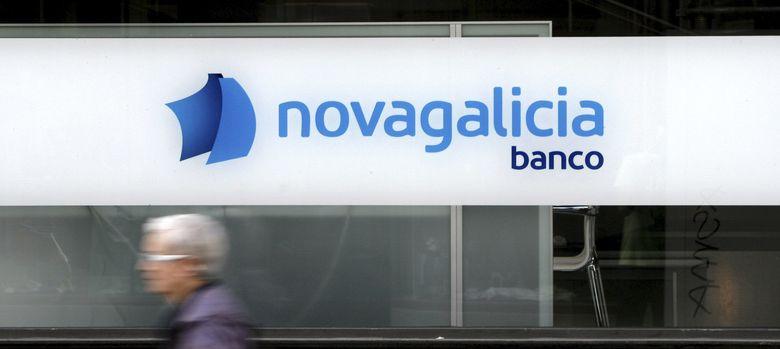 Foto: Una mujer pasa por delante de una oficina de Novagalicia Banco. (EFE)