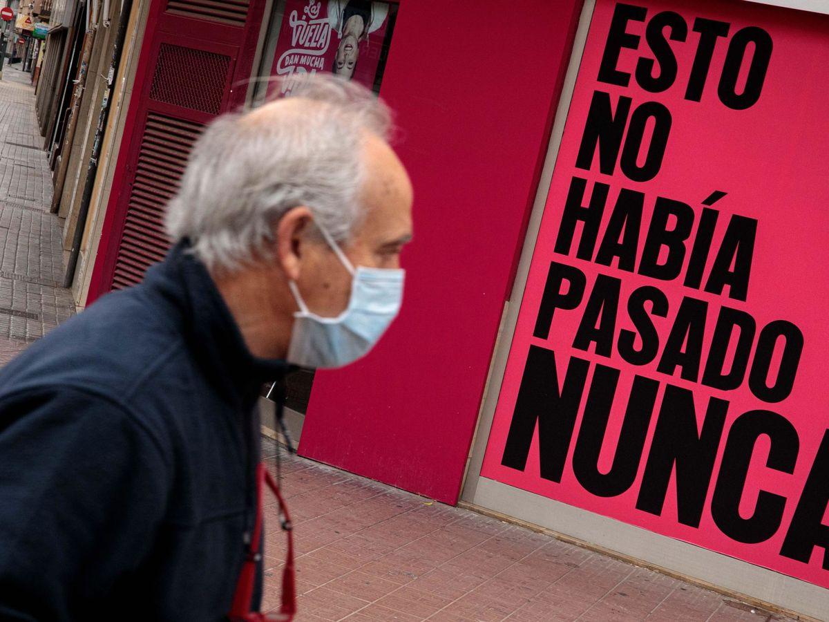 Foto: Un hombre con mascarilla camina por la calle durante la quinta jornada de confinamiento. (EFE)