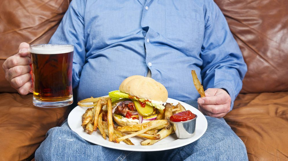 Foto: Un señor se come una hamburguesa en su sofá. (iStock)