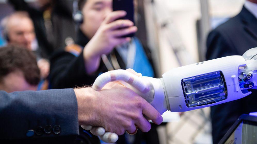 Foto: Un empleado estrecha la mano de un robot en la Feria Industrial en la ciudad alemana de Hannover. (EFE)