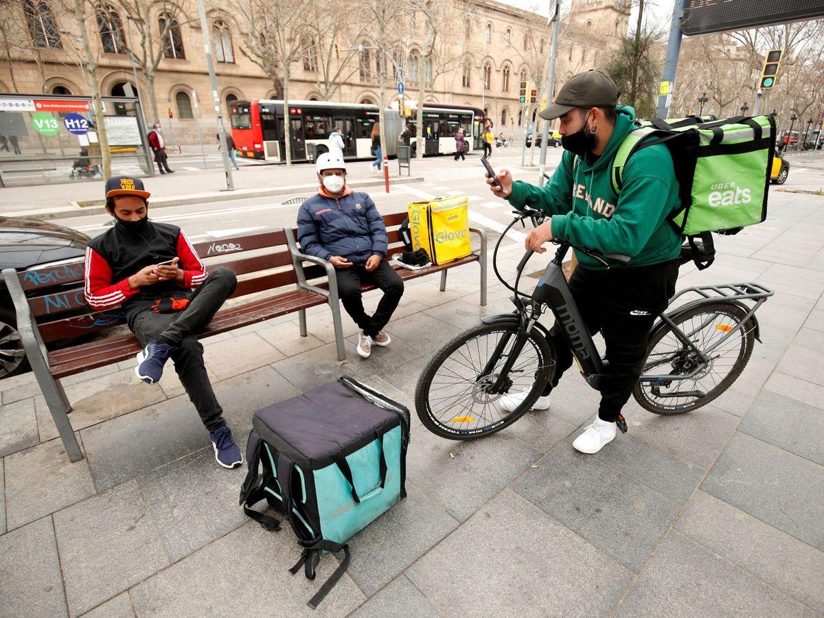 Foto: Repartidores de Glovo, Uber Eats y Deliveroo esperan en Barcelona. (Reuters)