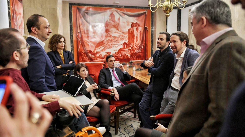 Foto: Pedro Sánchez y Pablo Iglesias con sus equipos, tras la firma del pacto de PSOE y UP, este 30 de diciembre en el Congreso. (Dani Gago | Twitter)