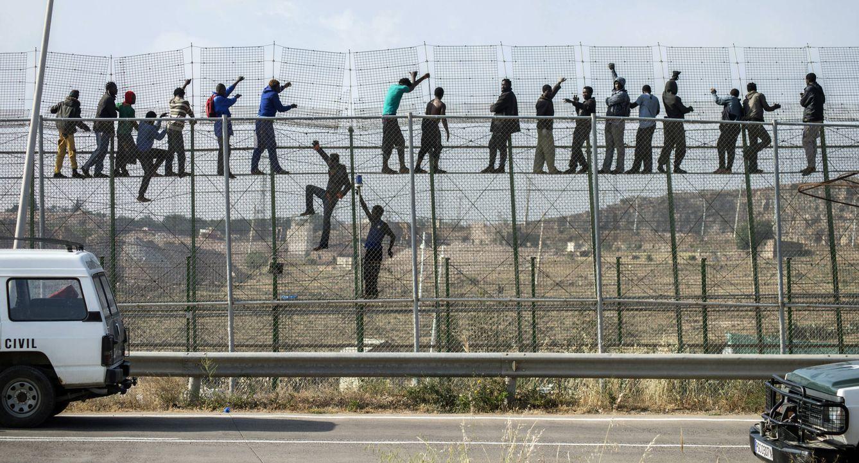 Foto: Migrantes africanos encaramados a la valla de Melilla tras intentar entrar en territorio español, en mayo de 2014 (Reuters).