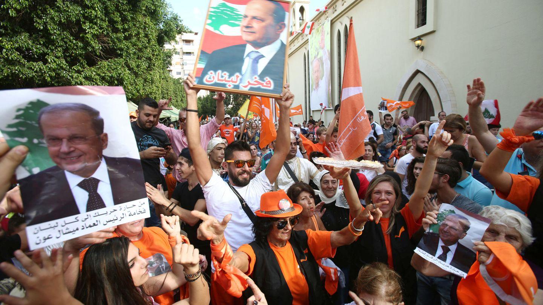 Miembros del Movimiento Patriótico Libre enarbolan imágenes de Michel Aoun tras conocerse su nombramiento (Reuters)