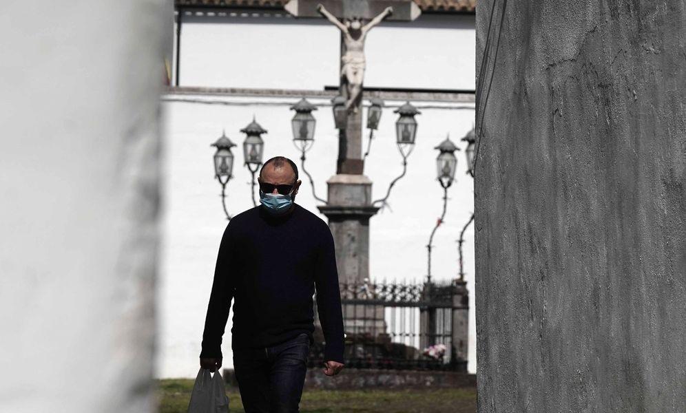Foto: Un hombre camina con la bolsa de la compra a su paso por la Plaza de Capuchinos de Córdoba, con la imagen del Cristo de los Faroles al fondo. (EFE)