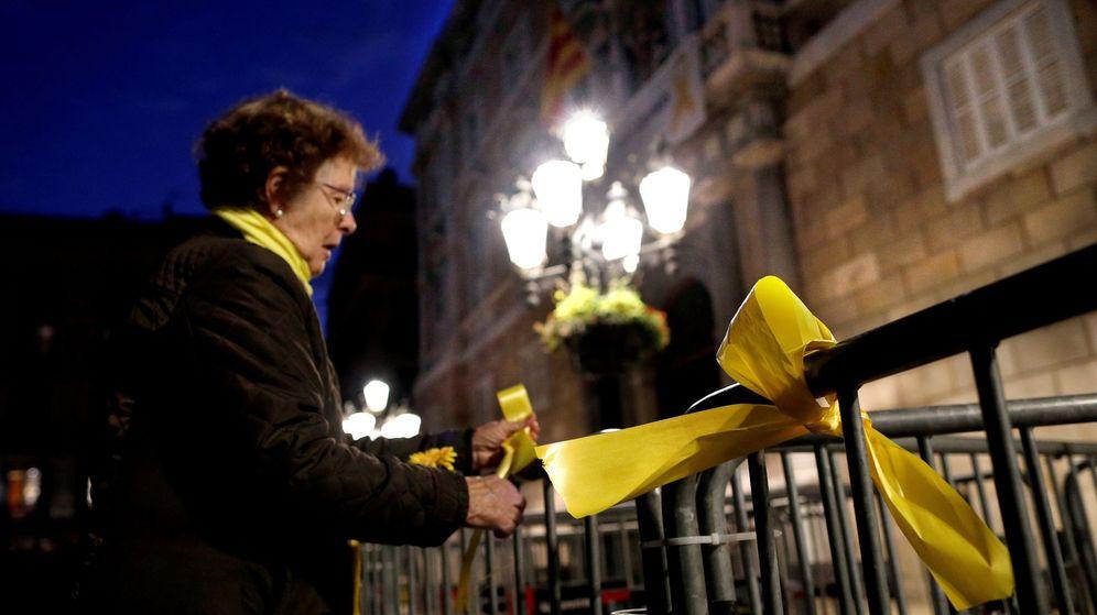 Foto: Una mujer coloca lazos amarillos en las vallas que rodean el Palau de la Generalitat en cuya fachada permanece la pancarta que pide la liberación de los políticos presos y un lazo amarillo. (EFE)