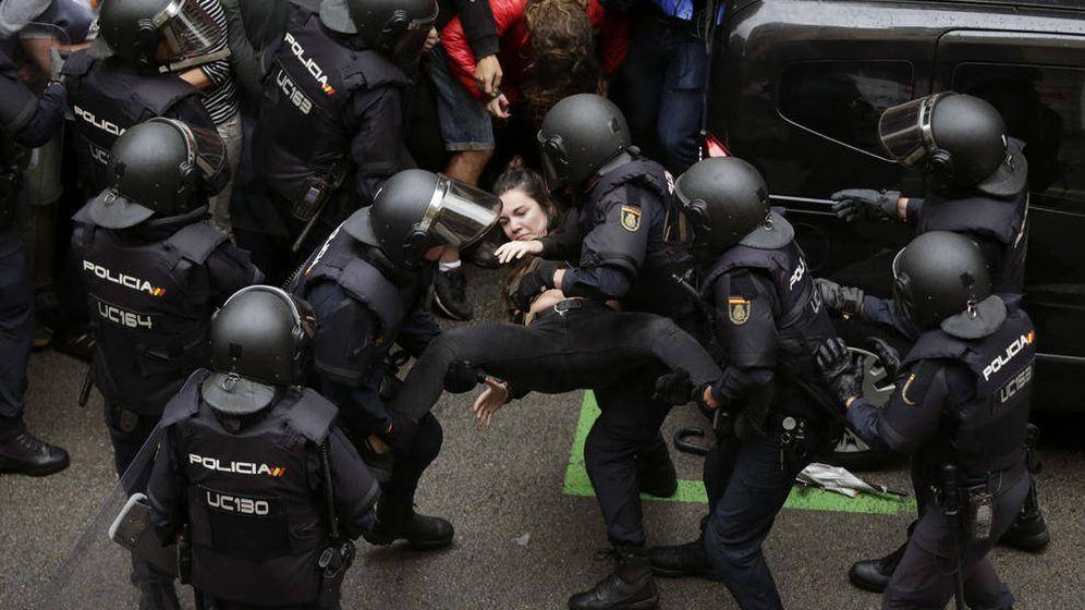 Foto: Agentes de la Policía forman un cordón policial en el colegio Ramón Llull y se llevan a una chica. (EFE)