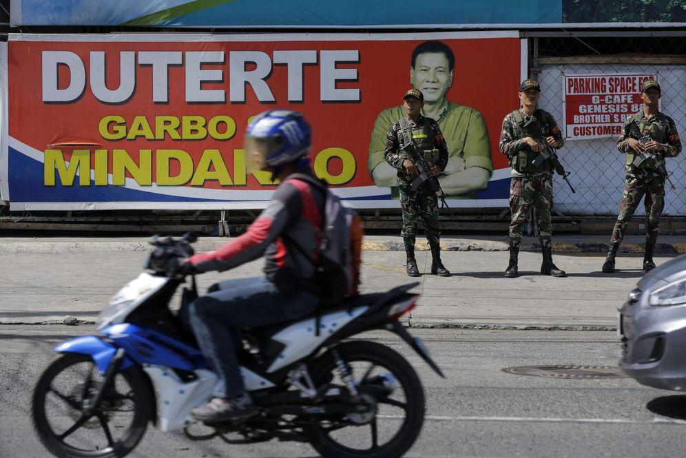 Foto: Soldados filipinos frente a un cartel electoral de Rodrigo Duterte en Davao, Mindanao, en mayo de 2016 (EFE)