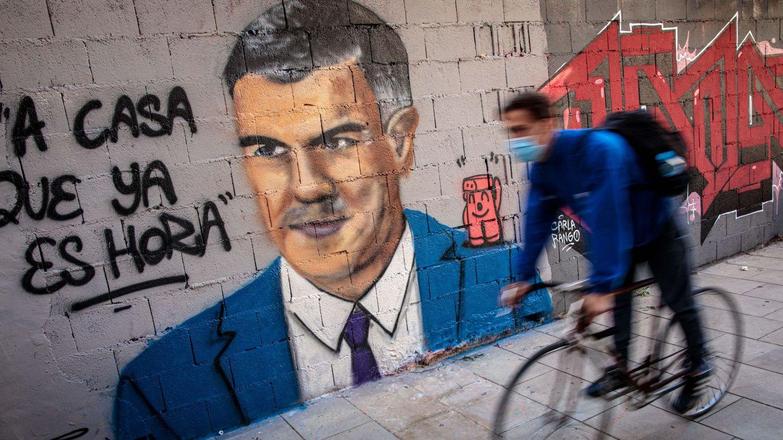 Una persona en bicicleta pasa frente a una pintura mural del artista urbano J. Warx. (EFE)