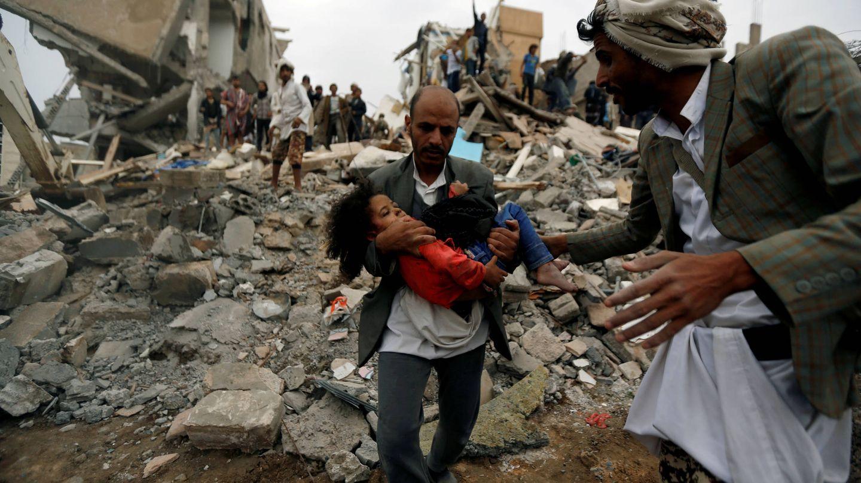 Un hombre socorre a una niña tras un bombardeo saudí en Saná, Yemen. (Reuters)