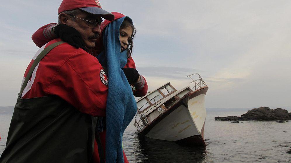 Foto: Un miembro de la Cruz Roja ayuda a una de los refugiados que viajaban en una embarcación a su llegada a la isla de Lesbos. (EFE)