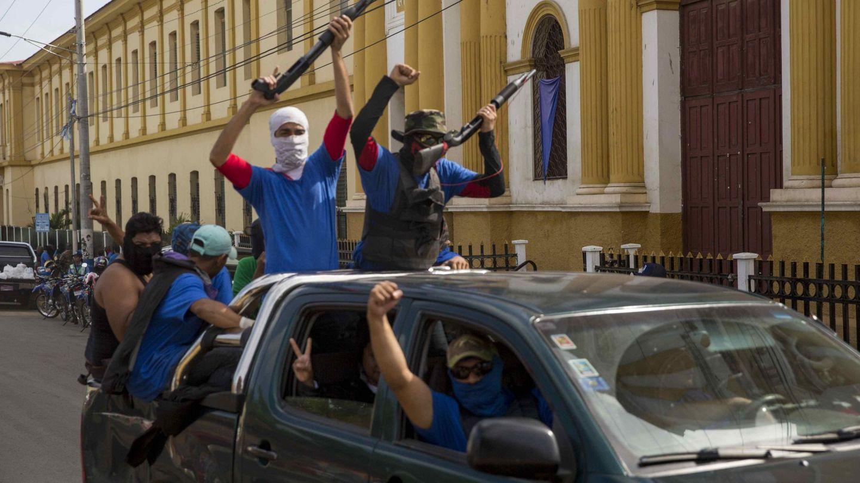 Personas con la cara tapada que apoyan a Ortega vigilan las calles de Masaya. (EFE)