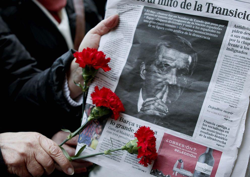 Foto: Una persona sostiene tres claveles ante un portada de un periódico con la imagen de Alfonso Suárez. (EFE)