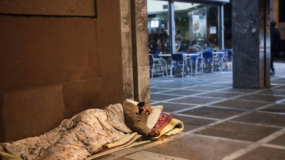 Foto: Un hombre 'sin techo' duerme en la acera, junto a una cafetería. (EFE)