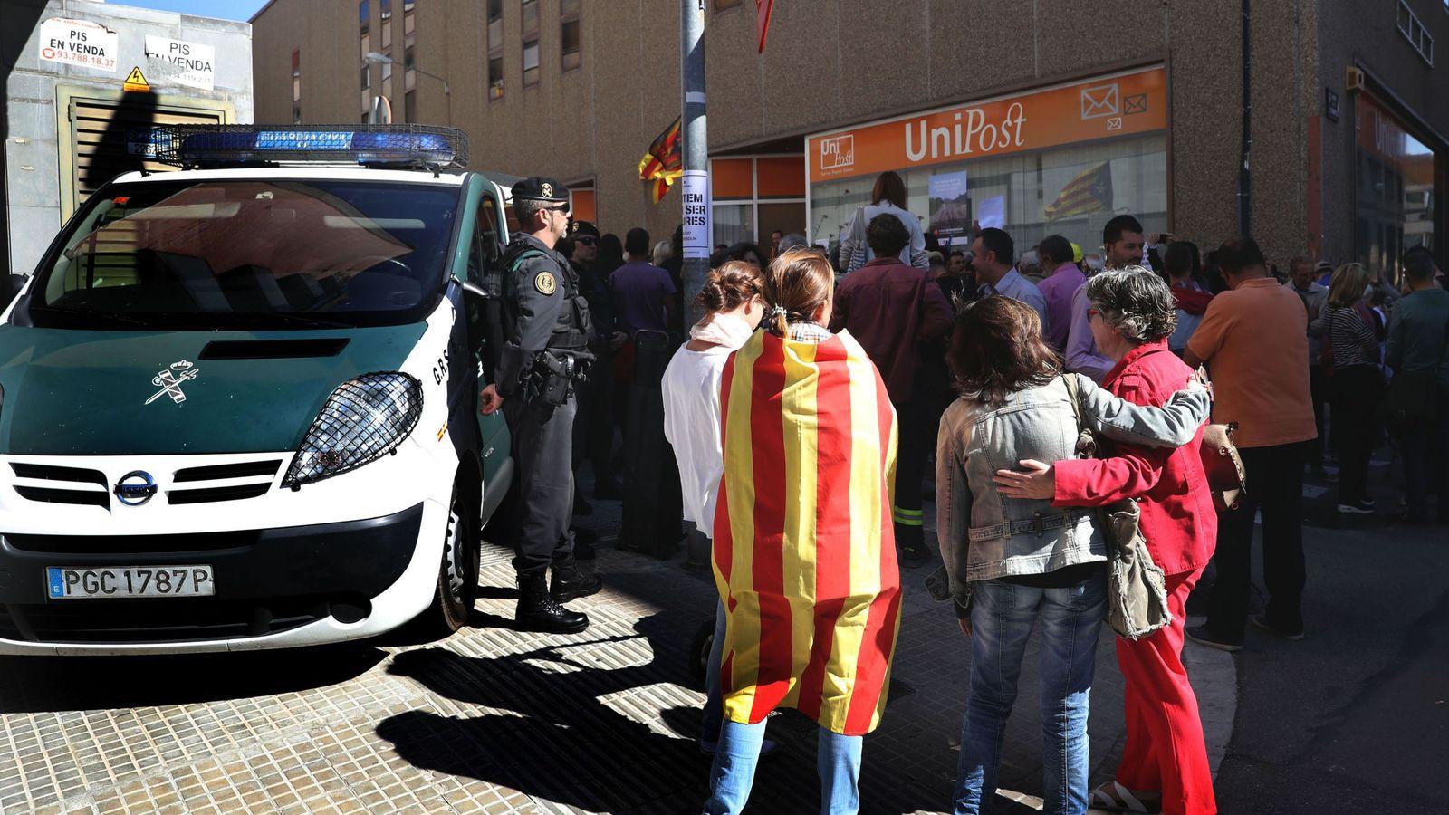 Foto: Numerosas personas permanecen ante la oficina de la empresa de mensajería Unipost en Terrassa. (EFE)