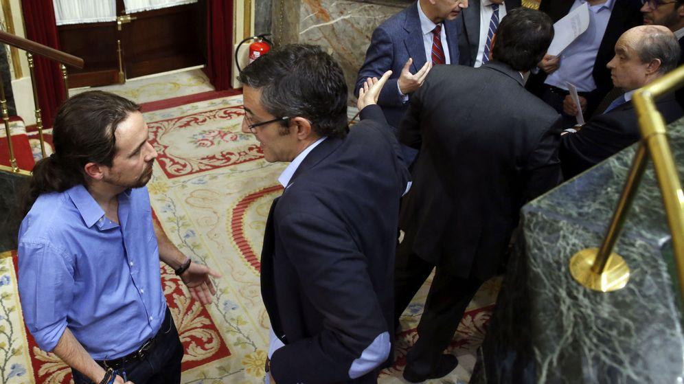 Foto: El secretario general de Podemos, Pablo Iglesias, y el diputado socialista Eduardo Madina conversan tras un pleno del Congreso. (Efe)