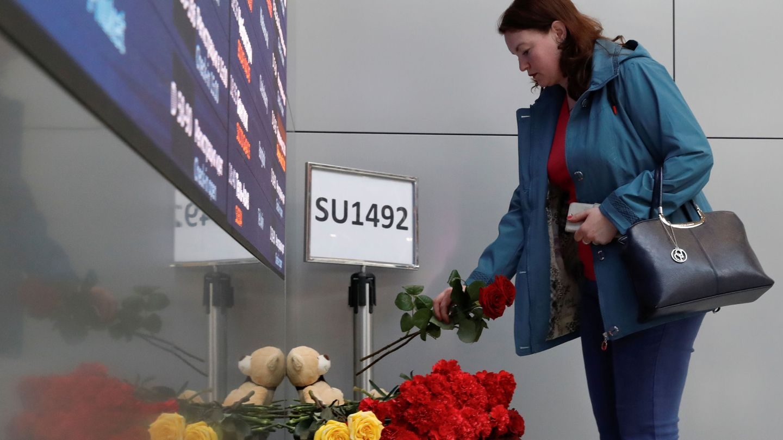 Una mujer deja flores en el aeropuerto de Sheremetyevo de Moscú en memoria de los fallecidos. (Reuters)