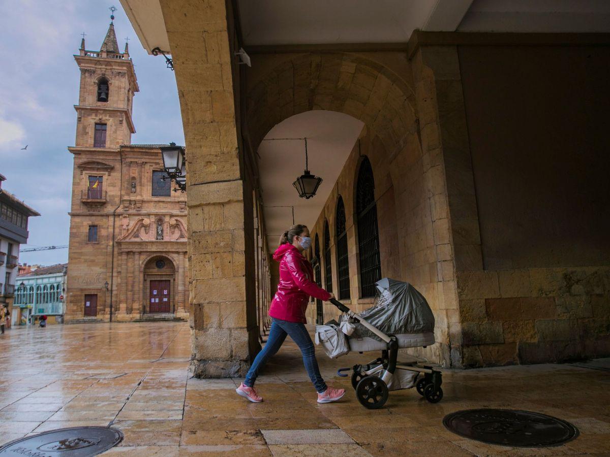 Foto: Un mujer pasea a su hijo por una calle de Oviedo. (EFE)