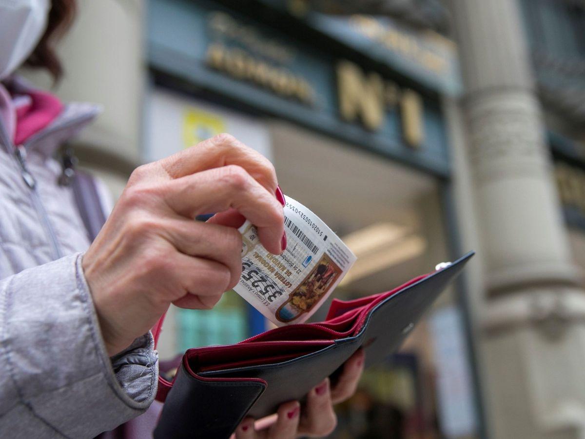 Foto: Una mujer guarda un décimo de la Lotería de Navidad en la cartera (EFE)