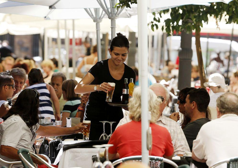 Foto: Una mujer joven trabajando de camarera en una terraza del centro de Valencia (EFE)