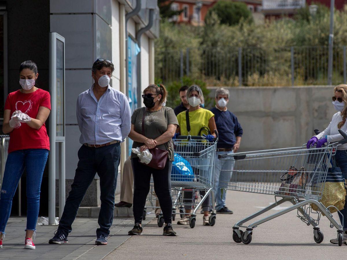 Foto: Un grupo de personas acude al supermercado con mascarillas. (EFE)