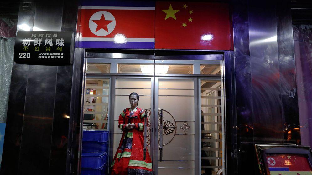 Foto: Una mujer en un vestido tradicional en la puerta de un restaurante norcoreano a orillas del río Yalu, en la frontera entre China y Corea del Norte, el 30 de marzo de 2017. (Reuters)