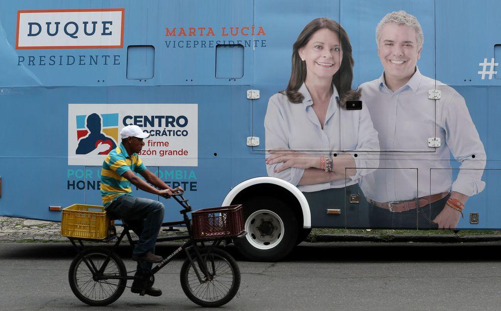 Foto: Un hombre pasa frente a un autobús con publicidad del candidato a la Presidencia de Colombia Iván Duque (d), en Bogotá. (EFE)