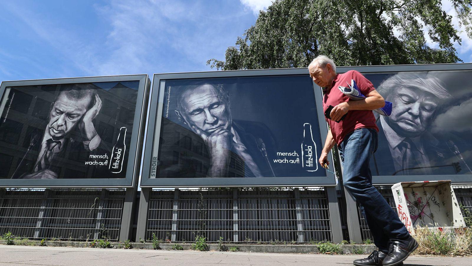 Foto: Un hombre pasa ante un cartel con los rostros de Trump, Putin y Erdogan, en Hamburgo. (Reuters)