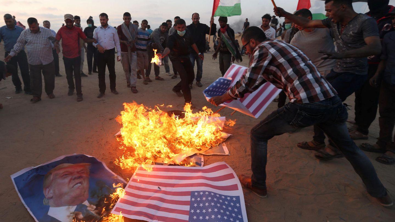 Manifestantes palestinos queman retratos de Donald Trump y banderas de EEUU durante la conmemoración del 70º aniversario de la Nakba, el 15 de mayo de 2018. (Reuters)