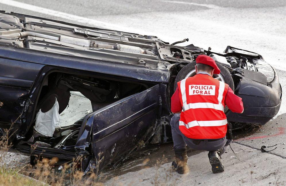 Foto: Un Policía Foral inspecciona un vehículo tras un accidente. (EFE)