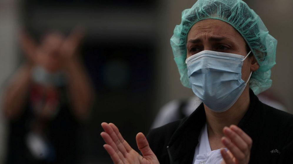 Foto: Una trabajadora sanitaria del hospital La Paz aplaude a las puertas del centro (REUTERS)