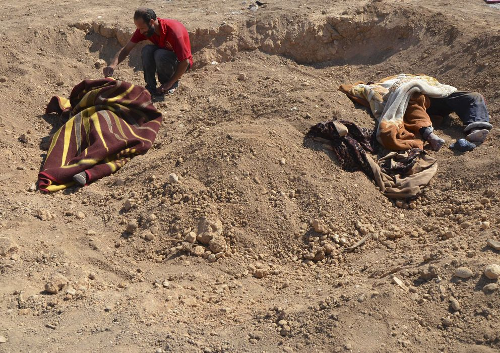 Foto: Un hombre junto a cadáveres de civiles víctimas del supuesto ataque tóxico en las cercanías de Damasco (Reuters).