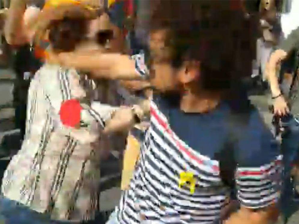 Foto: El hombre que arrebató la bandera a la mujer, en el momento de propinarle un puñetazo. (Foto: Twitter)